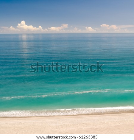 Beautiful landscape of beach with green water and blue sky.