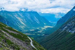 Beautiful landscape of blue mountains from the Trollstigen or Troll Stairs viewpoint, to which the famous tourist serpentine road leads. Andalsnes, Norway.