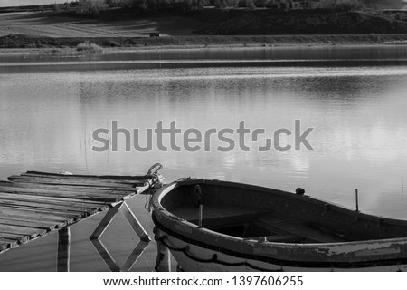 Beautiful Landscape of Boat and Pier. Cockboat on the lake. Wooden pier and Dinghy. Old fishing boat. Sandal on the water. Black and White picture, Zara/Sivas.
