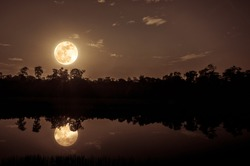 Beautiful landscape of colorful sky and clouds. Full moon with reflection above silhouette of trees and river. Serenity nature in gloaming time. Outdoors at nighttime. The moon taken with my camera.