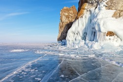 Beautiful landscape of frozen lake Baikal on a Sunny day in February. Blue ice with cracks and hummocks near the icy rocks of Olkhon island. Winter holidays, ice travel. Natural background