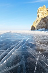 Beautiful landscape of frozen lake Baikal on a Sunny day in February. Ice road to Cape Hoboy past the rocks of Three Brothers at Olkhon island. Winter holidays, ice travel. Natural background