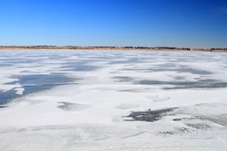 Beautiful landscape of frozen lake covered with snow and ice