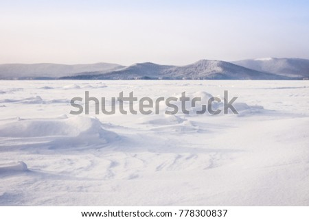 Beautiful landscape of frozen lake covered with snow and ice. Turgoyak Lake in Southern Urals, Russia.