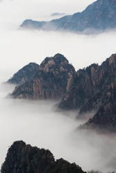 Beautiful landscape of Huangshan National Park in China with rime sea of cloud and fog after sunrise. It's known for pine tree forest and rime sea of cloud.