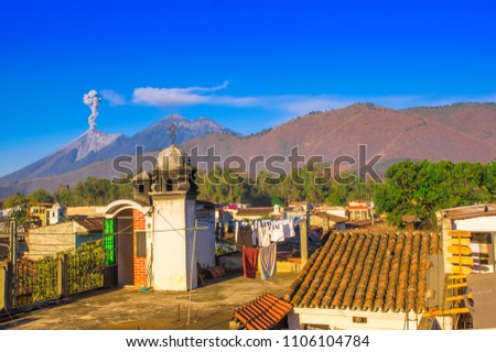Beautiful landscape of huge mountain in process of aruption with a column of ash, view from the rooftops of the building in Antigua city in gorgeous sunny day and blue sky