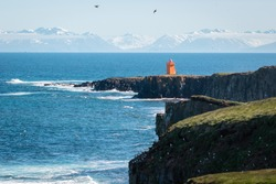 Beautiful landscape of Lighthouse in Grimsey island in Arctic circle in Iceland, blue ocean and cliffs many birds flying with blue sky and mountains of the main land visible on the background
