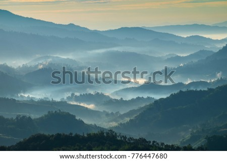 Beautiful Landscape of mountain layer in morning sun ray and winter fog at Chiangrai, Thailand #776447680