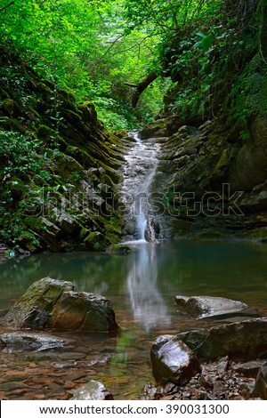 Beautiful landscape of waterfall in deep forest with big brown stones at foreground and tree branches background. Amazing view at fast water stream in tropical forest scenery and small green pond.
