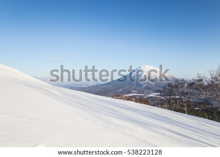 Beautiful landscape of white snow hill on front of Mt.Yotei, the active stratovolcano in, Hokkaido, Japan. The winter scene under blue sky from Ski-resort in Niseko Annupuri area #538223128
