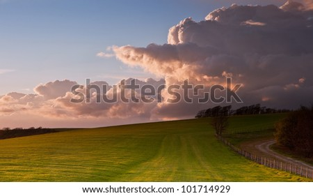 Beautiful landscape over agricultural fields with moody sky and invigorating sunlight