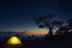 Beautiful Landscape Panoramic Nature View of Illuminated Yellow Camping Tent of Camper in the Forest at the Cliff with Milky Way and Starry Night Sky Background