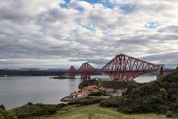 Beautiful landscape showing the Forth Bridge in Edinburgh city center in Scotland. Unesco world heritage site in Northern Europe. The small village of South Queensferry in the foreground