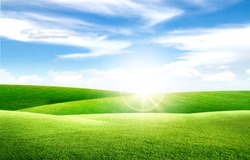 Beautiful landscape view of Green grass natural meadow field and little hill with white clouds and blue sky in summer seasonal.