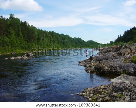 Beautiful landscape view of river in a green forest. Fishing man