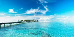 Beautiful landscape with bridge to pier. Color fusion of ocean and sky. Light ripples on amazingly clear water. Perspective receding into distance. Image fine vacation on summer. Relax and rest.