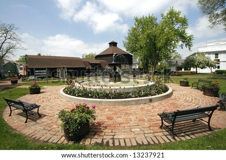beautiful landscape with fountain, trees, flowers, benches, shrubs