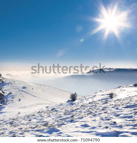 Beautiful landscape with snow-covered mountains, the sun and clouds