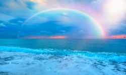 Beautiful landscape with turquoise sea, rainbow over the sea at sunset