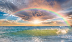 Beautiful landscape with turquoise sea with double sided rainbow at sunset