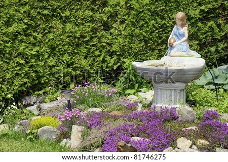 Beautiful landscaping/ front yard curb appeal: young woman statue pouring water into a fountain, surrounded by a variety of flowers with thyme in purple bloom and a wall of cedar trees.