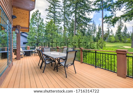 Beautiful large cabin home  with large wooden deck and chairs with table overlooking golf course. Stock photo ©