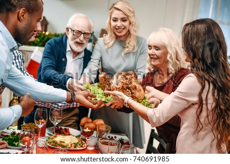 beautiful large family holding christmas turkey for holiday dinner #740691985