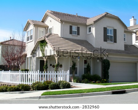 Beautiful large home with white picket fence. Blue sky with wispy clouds.