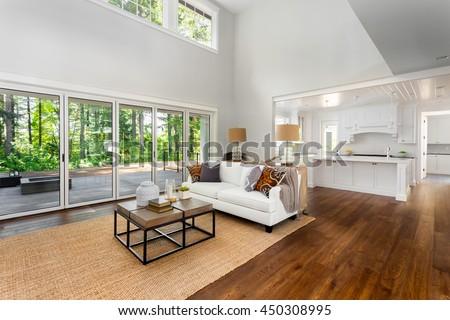 Beautiful large living room with hardwood floors, couch, and sliding glass doors in new luxury home.Vaulted ceiling and loft style second floor frame the scene, with foyer, dining room, and kitchen
