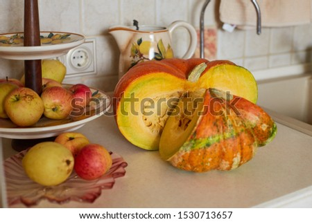 Beautiful large pumpkin with large seeds and red apples on a fruit stand on a table in the kitchen