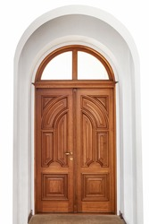 Beautiful large wooden door on a white background wall. Hand carved, vertical pattern