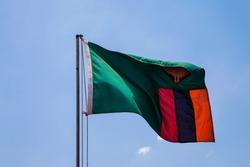 Beautiful large zambian flag waving in the wind against blue sky. zambian Flag Waving Against Blue Sky. Flag of zambia waving, against blue sky
