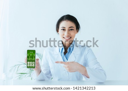 beautiful latin doctor pointing with finger at smartphone with heartbeat rate on screen heartbeat rate app #1421342213