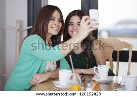 Beautiful latin friends taking a picture with their phone