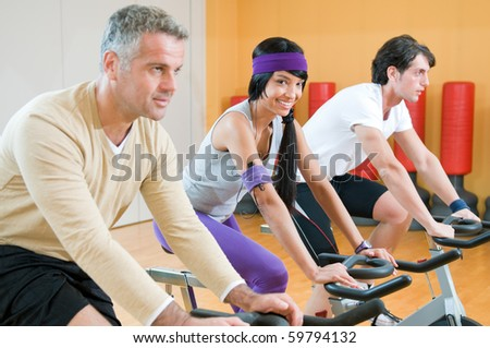 Beautiful latin girl smiling and looking at camera while exercising with bicycles in group at gym