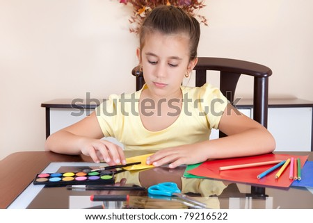Beautiful latin girl working on her art project at home with some art supplies on the table