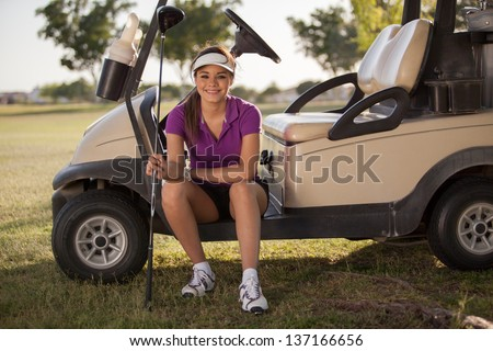 Beautiful Latin golfer sitting in a golf cart and smiling