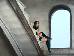 beautiful latin hispanic female dancer resting on stairway. young girl in black dress and  sitting on concrete stairs