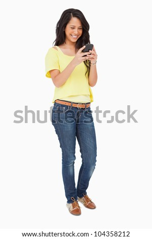 Beautiful Latin laughing while using a smartphone against white background