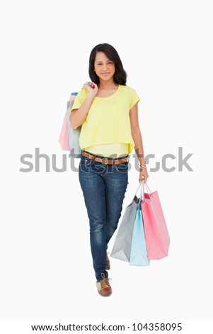 Beautiful Latin student walking with shopping bags against white background