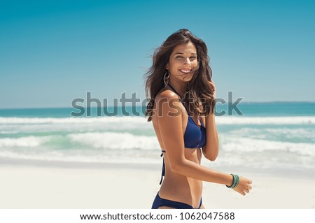 Beautiful latin woman in blue bikini on tropical beach. Portrait of happy young woman smiling at sea. Brunette tanned girl in swimwear enjoying and walking on beach.