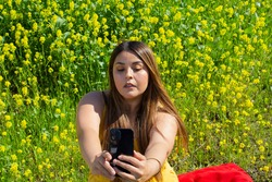 beautiful latin woman taking a selfie with her cell phone at picnic in landscape full of yellow flowers. fat model