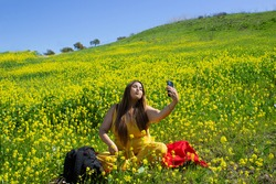 beautiful latin woman taking a selfie with her cell phone at picnic in landscape full of yellow flowers. chubby woman