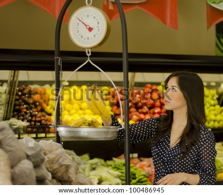 Beautiful latin woman weighing fruits on a scale in a supermarket