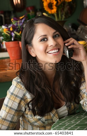 Beautiful Latina Woman at table in Kitchen on Phone