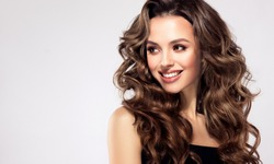 Beautiful laughing brunette model  girl  with long curly  hair . Smiling  woman hairstyle wavy curls .  Fashion , beauty and make up portrait
