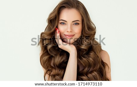 Beautiful laughing brunette model  girl  with long curly  hair . Smiling  woman hairstyle wavy curls . Red  nails manicure .    Fashion , beauty and makeup portrait  ストックフォト ©