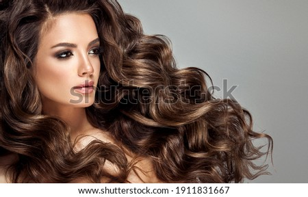 Beautiful laughing brunette model  girl  with long curly  hair . Smiling  woman hairstyle wavy curls .     Fashion , beauty and makeup portrait