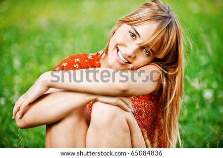 Beautiful laughing girl in red dress sits on green grass.