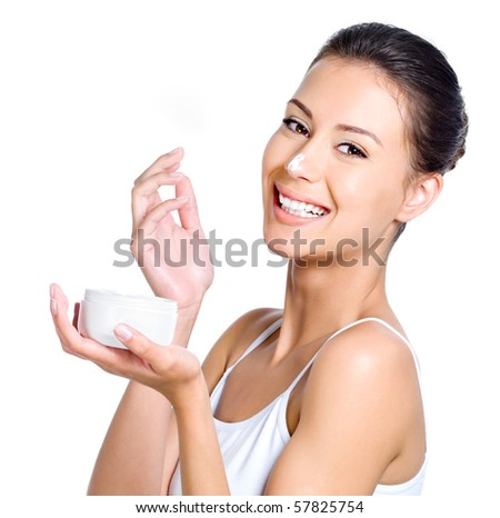 Beautiful laughing young woman with facial cream on her nose isolated on white